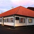 Māja ar baltām sienām un sarkanu jumtu